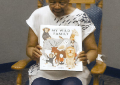 Monique reading My Wild Family - cropped